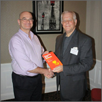 A prize winner collects his copy of Branding Your Business at an EADIM event.